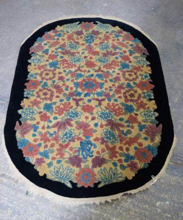 A Art Deco Chinese Black border floral oval rug. 150 x 96cm.