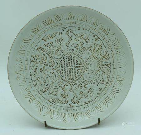 A Chinese porcelain dish decorated with Kuyi and longevity symbols in relief. 5 x 28cm.