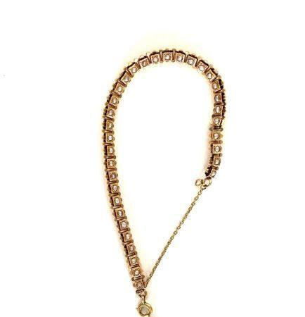 BRACELET en or jaune (750 millièmes) articulé serti de demi-perles blanches retenant une BRELOQ