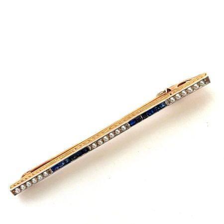 BROCHE barrette en or jaune (750 millièmes) serti de saphirs calibrés et de petites demi-perles