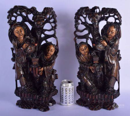 A RARE PAIR OF 19TH CENTURY CHINESE SILVER INLAID HARDWOOD FIGURAL GROUPS modelled pouring tea upon