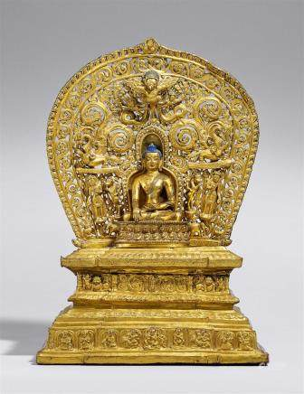 A Tibetan gilt bronze figure of Buddha Shakyamuni on an exremly rare gilt copper repoussé throne with aureole. 15th century