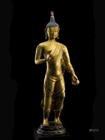 A GILT COPPER ALLOY FIGURE OF STANDING BUDDHA CENTRAL TIBET, 11TH/12TH CENTURY