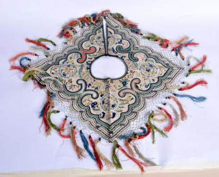 AN EARLY 20TH CENTURY CHINESE SILK WORK CHILDS SHOULDER AND NECK PIECE decorated with foliage and landscapes. 65 cm wide.
