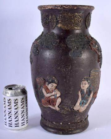 A 19TH CENTURY JAPANESE MEIJI PERIOD PAINTED TERRACOTTA VASE decorated in relief with figures and trees. 34 cm x 14 cm.