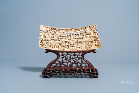 A Chinese richly carved ivory plaque with an animated city view on a wooden base, Canton, 19th C.