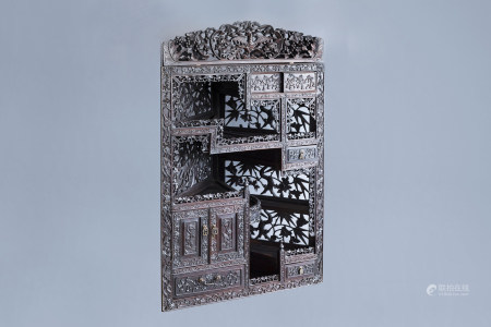 A Chinese carved wooden open worked corner display cabinet with floral design, 19th/20th C.