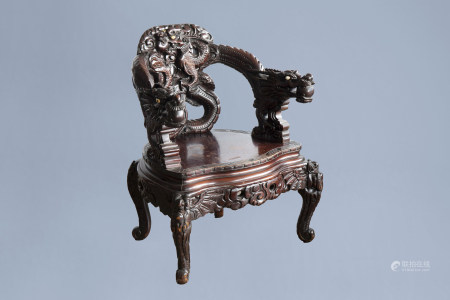 A Chinese or Japanese carved wooden 'dragons' chair, 20th C.