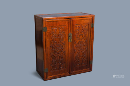 A Chinese wooden two-door cupboard with carved floral panels, 19th C.