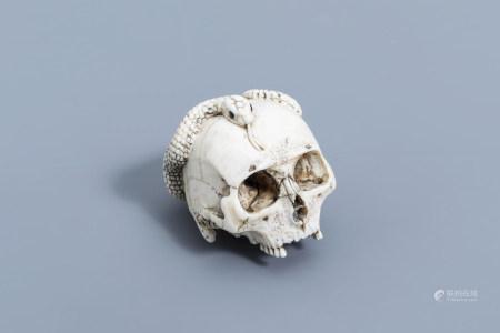 A Japanese ivory okimono of a human skull entwined with a snake, Meiji, ca. 1900