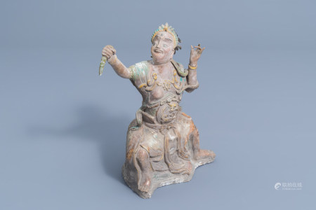 A Chinese partly glazed earthenware figure with a snake, Ming or later