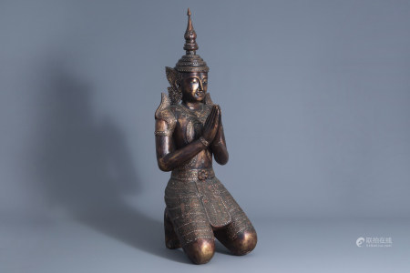 A patinated and gilt wooden kneeling Buddha figure, Thailand, 19th/20th C.