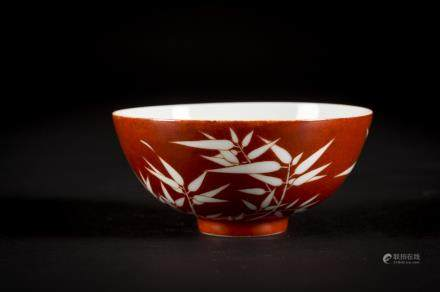 A Chinese porcelain bowl with coral red bamboo decoration, Yongzheng mark and possibly of the period (12x6cm)