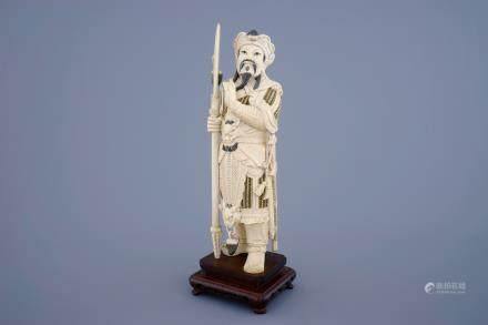 A Chinese carved ivory figure of a warrior on a wooden base, late 19th C.