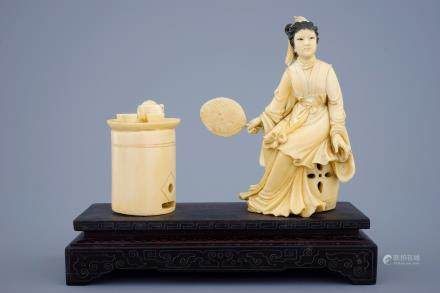 A Chinese carved ivory group of a lady near a tea table on a wood base, 19th C.