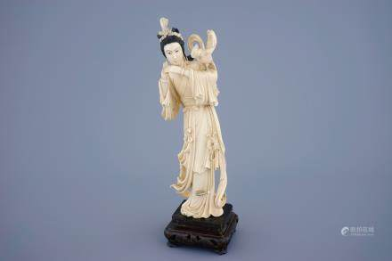 A Chinese carved ivory figure of Guanyin with a bird on wooden base, 19th C.