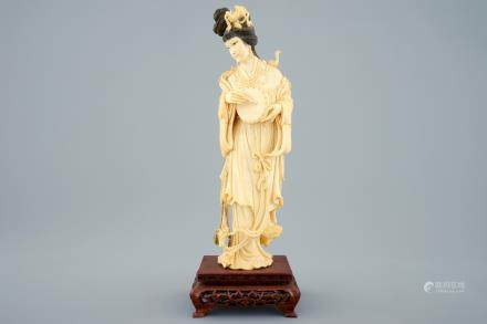 A Chinese carved ivory figure of a lady with hand drum on wooden base, early 20th C.