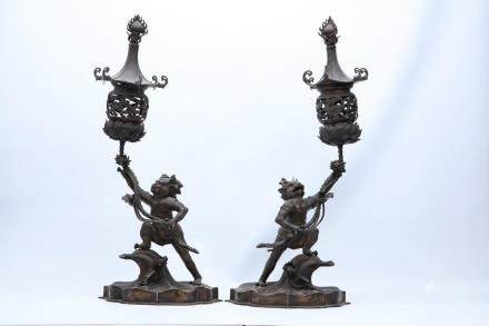 A PAIR OF BRONZE CANDLE HOLDERS.
