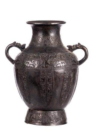A Chinese archaic bronze vase, relief decorated with key patterns and mythical animals, the handles dragon head shaped, H 52 cm