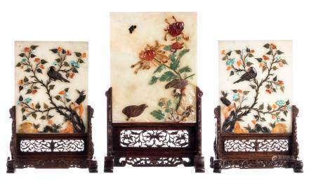 Three Chinese table screens with jade plaques, decorated with semi-precious stones, depicting birds on flower branches on sculptured wooden stands, H 35,5 - 43,5 cm (slight damage)