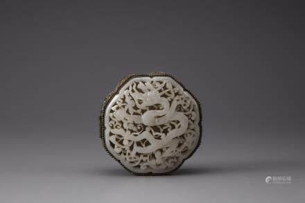 A white jade 'dragon' plaque inset into a gilt filigree box