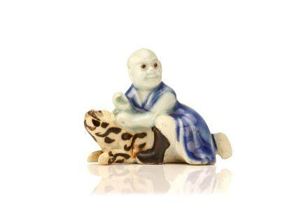 A CHINESE PORCELAIN FIGURE OF PINDOLA WITH A TIGER