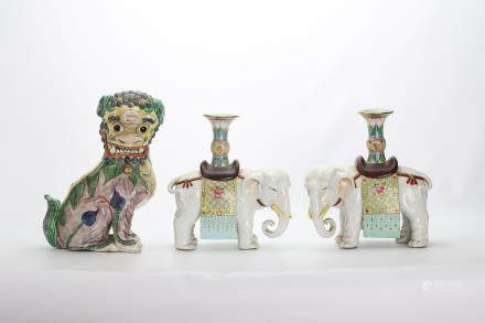 A CHINESE FAMILLE VERTE MODEL OF A BUDDHIST LION DOG, TOGETHER WITH TWO FAMILLE ROSE €˜ELEPHANT€™ CANDLE STICKS