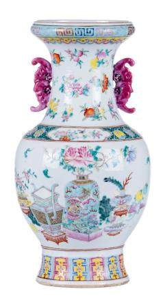 A Chinese famille rose vase, overall decorated with flower vases, antiquities and fruits, the handles bat shaped, 19thC, H 42,5 cm (crack to the bottom)