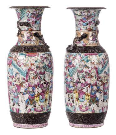 A pair of Chinese famille rose stoneware vases, overall decorated with warriors, dragon relief decorated, marked, 19thC, H 61 cm (chips)