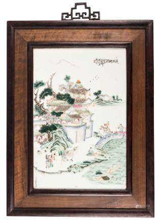 A Chinese polychrome porcelain plaque, decorated with figures in a landscape, signed and mounted in a wooden frame, 25,5 x 40 cm (without frame)