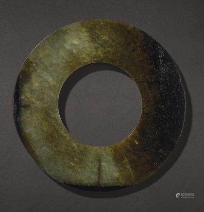 A YELLOWISH-GREEN AND BROWN JADE DISC, HUAN PROBABLY SHANG DYNASTY