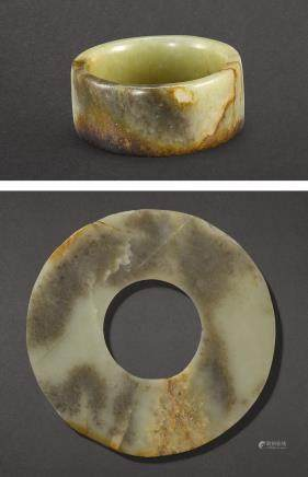 A CELADON AND BROWN JADE CYLINDER OR BRACELET AND A JADE DISC, HUAN NEOLITHIC PERIOD – SHANG DYNASTY