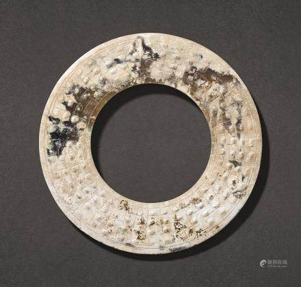 A PARTLY CALCIFIED CELADON AND BROWN JADE DISC, HUAN LATE WARRING STATES PERIOD – EARLY WESTERN HAN DYNASTY