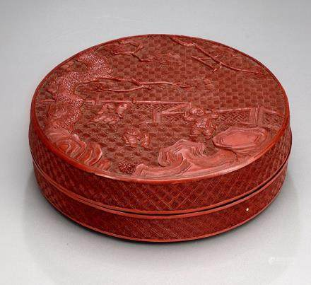 A CIRCULAR RED LACQUER BOX WITH A CARVED SCENE OF PLAYING BOYS