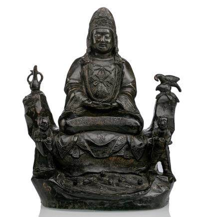 A BRONZE MODEL OF GUANYIN ON A ROCK WITH ATTENDANTS