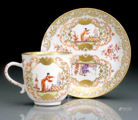 "A RARE CUP AND SAUCER WITH GERMAN ""HAUSMALEREI"" IN THE STYLE OF EARLY MEISSEN WARE"