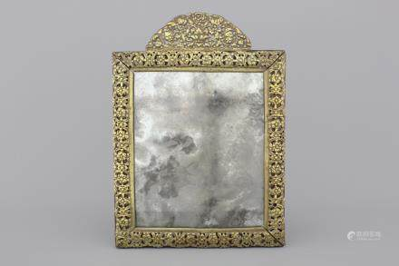 A Louis XIII gilt brass frame mirror, 17th C.