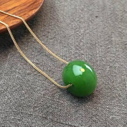 A NATURAL BEAD YANGLV HETIAN GREEN JADE PENDANT