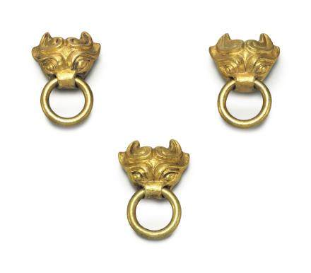 A SET OF THREE MINIATURE GOLD MASK-FORM HANDLES