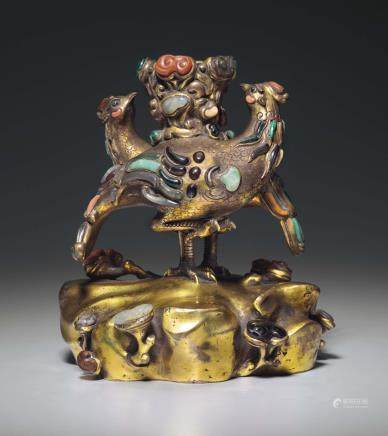 A RARE CORAL, HARDSTONE AND GLASS-INLAID GILT-BRONZE PHOENIX-FORM CANDLEHOLDER