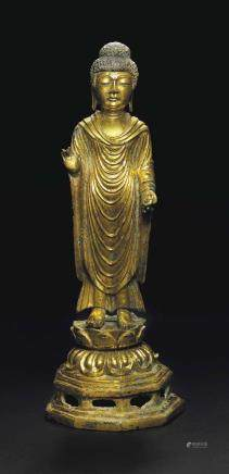A RARE AND IMPORTANT GILT-BRONZE STANDING FIGURE OF BUDDHA
