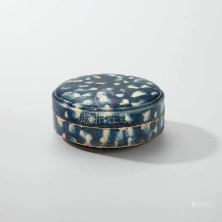 A SMALL BLUE-GLAZED RESERVE-DECORATED CIRCULAR BOX AND COVER