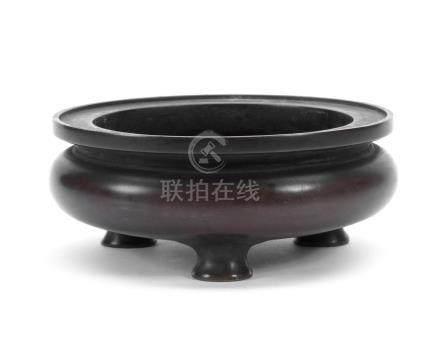 A bronze tripod incense burner