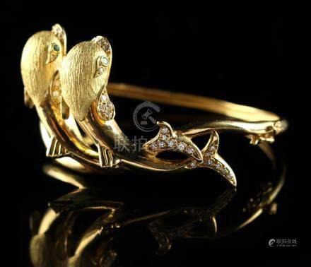 An 18ct yellow gold hinged bracelet modelled with two stylised dolphins set with emerald eyes, the