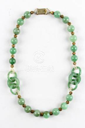 A Chinese jadeite bead & triple ring necklace, with gilt metal spacers, 16.5ins. (42cms.) long (