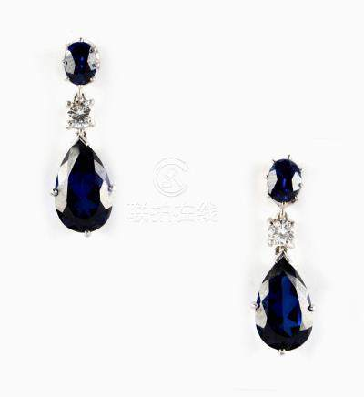 A pair of blue 'stone' & diamond pendant earrings, each with a pear shaped & an oval shaped blue '