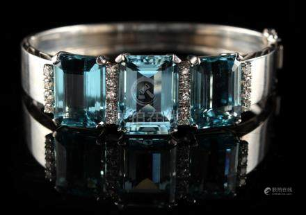 A good French white gold hinged bracelet set with three large aquamarines bordered by rows of