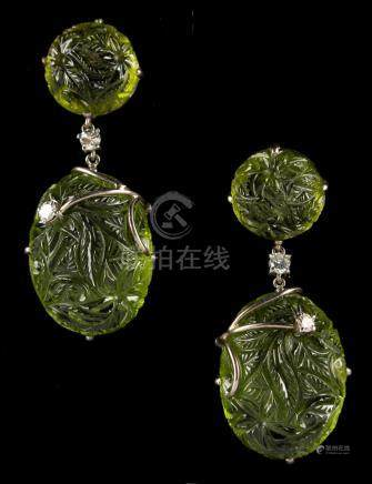 A pair of 18ct white gold carved peridot & diamond drop earrings, each with two oval peridot