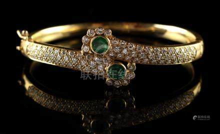 An unmarked yellow gold emerald & diamond hinged crossover bracelet, set with two round cut