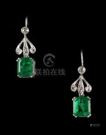 A pair of 18ct white gold emerald & diamond earrings, each with a rectangular cut emerald